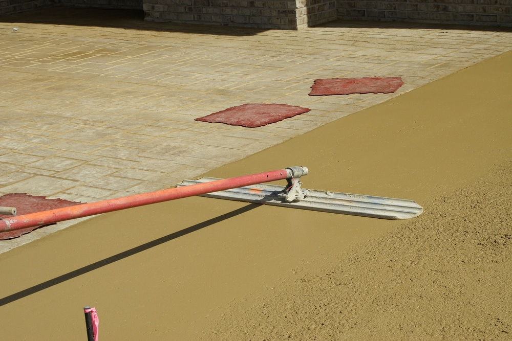 Worker resurfacing newly constructed concrete patio for commercial usage