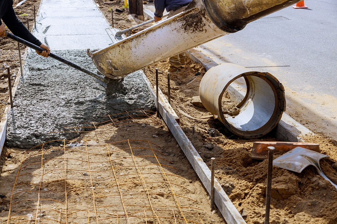 Workers installing Concrete mix using beam for sidewalk repair